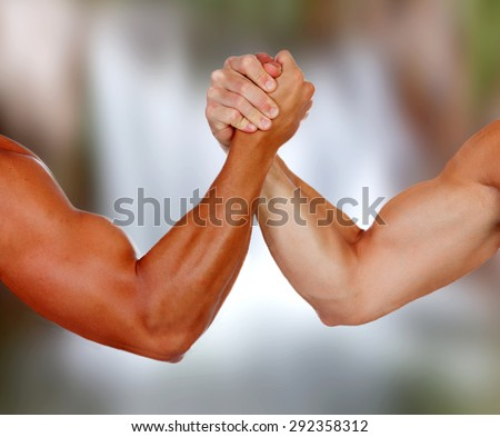 Strong arms with muscles taking a pulse with a blurred background - stock photo