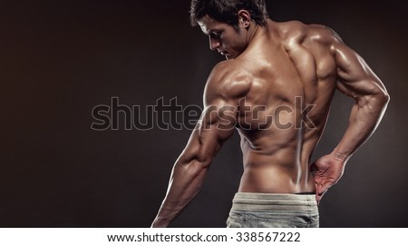 Strong Athletic Man Fitness Model posing back muscles, triceps, latissimus with copyspace - stock photo