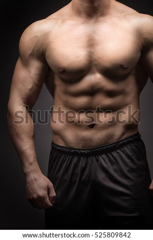 Strong Athletic Man Fitness Model Torso showing isolated on black background