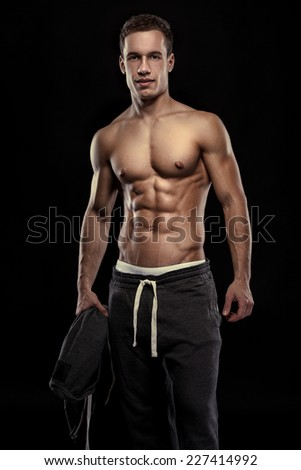 Strong Athletic Man Fitness Model Torso showing muscular body isolated on black background - stock photo