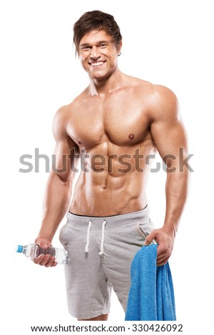 Strong Athletic Man Fitness Model Torso showing six pack abs. holding bottle of water and towel - stock photo
