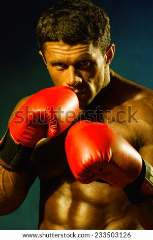 Strong athletic man in boxing gloves. Toned in shades of yellow image - stock photo
