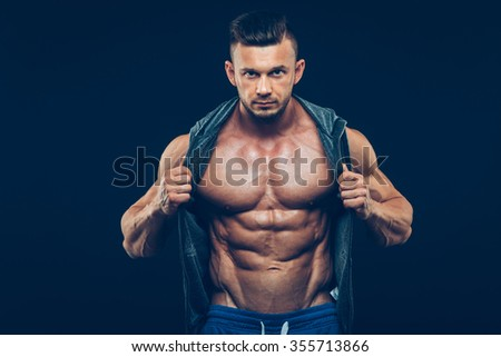 strong athletic man on black background. fitness