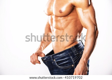 Strong Athletic Man showing muscular body and sixpack abs over white background.Muscular man on white background.Muscular man measuring his waistline - stock photo