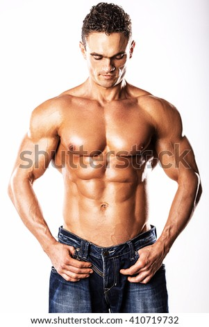 Strong Athletic Man showing muscular body and sixpack abs over white background.Muscular man on white background.Muscular man measuring his waistline