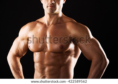 Strong Athletic Man showing muscular body on a black background.Muscular man on black background