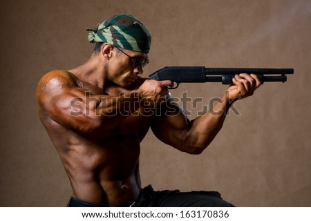 Strong athletic man with a gun. Special Forces soldier takes aim - stock photo