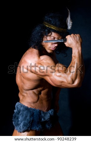 Strong athletic man with a knife on a black background - stock photo