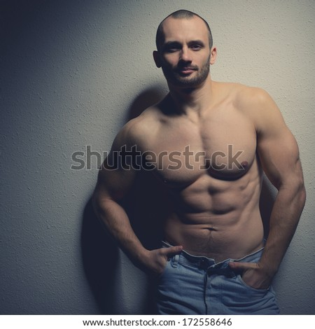 Strong athletic man with perfect body posing in studio on black background