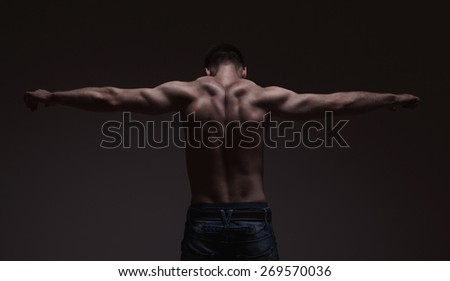 strong athletic mans back on dark gradient grey background - stock photo