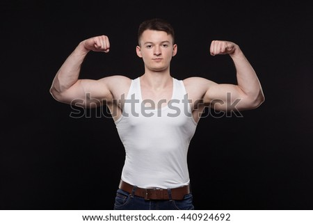 Strong athletic young  man on black background - stock photo