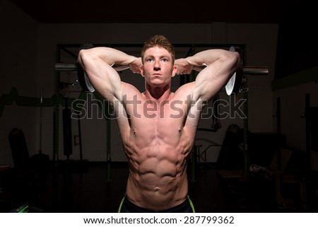 Strong attractive man working out with weights at a gym. Used dramatic lighting to convey determination, motivation, and focus.