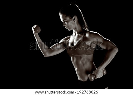 strong attractive woman athlete working with weights