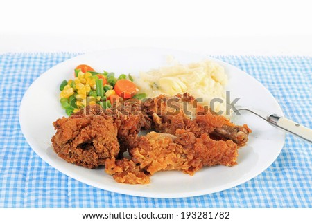 Strong back lighting on Three pieces of chicken with crunchy breading and deep-fried and served with mashed potatoes and mixed vegetable medley. - stock photo