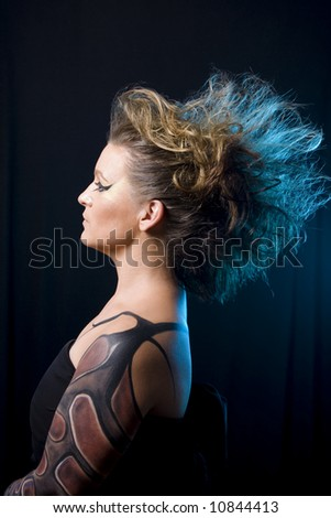 Strong, beautiful woman with extreme makeup - stock photo