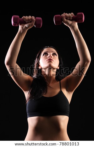 Strong beautiful young caucasian girl working out weight lifting, wearing black sports bra, taken against black background. - stock photo