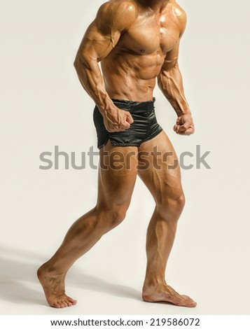 Strong bodybuilder man with perfect abs, shoulders,biceps, triceps and chest. Personal fitness trainer flexing his muscles - stock photo