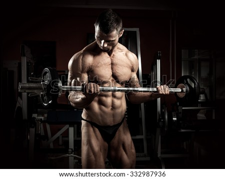 Strong bodybuilder with barbell in the gym