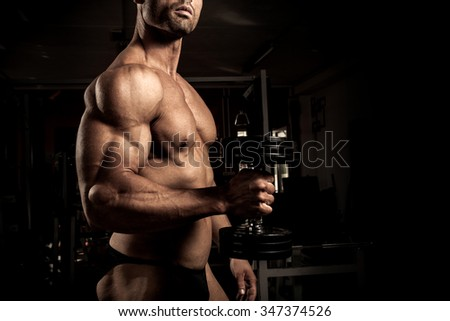 Strong bodybuilder with dumbbell in the gym
