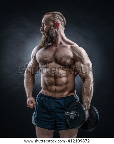 Strong bodybuilder with six pack, perfect abs, shoulders, biceps, triceps and chest. Power athletic bearded man posing with dumbbell.  - stock photo
