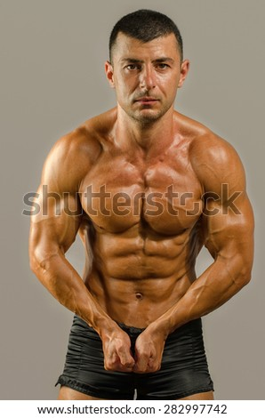 Strong bodybuilder with six pack.Strong bodybuilder man with perfect abs, shoulders,biceps, triceps and chest, personal fitness trainer flexing his muscles