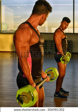 Strong bodybuilder with six pack.Strong bodybuilder man with perfect abs, shoulders,biceps, triceps and chest, personal fitness trainer flexing his muscles, training with a dumbbell in a gym - stock photo