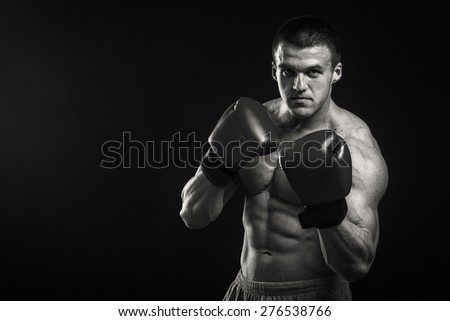 Strong boxer on a black background. Brawny guy in boxing gloves. - stock photo