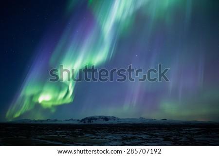 Strong bright purple green aurora noprthern lights over mountain lava plain, Thingvellir, Iceland - stock photo