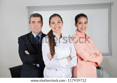 Strong business team smiling together in the office - stock photo
