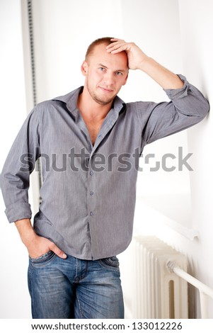 strong casually dressed man near white wall