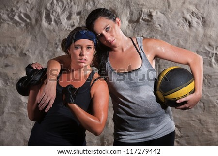 Strong Caucasian woman with workout partner flexing her bicep - stock photo