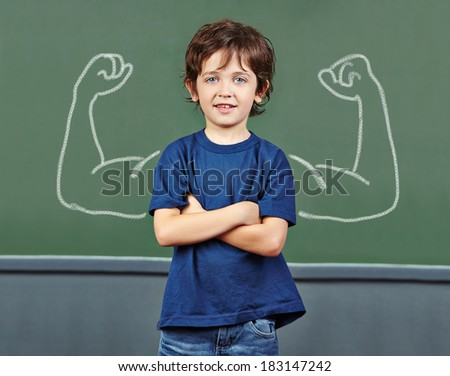 Strong child with muscles drawn on chalkboard in elementary school - stock photo