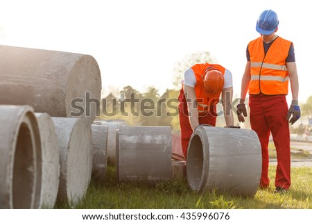 Strong construction worker rolling a concrete pipe - stock photo