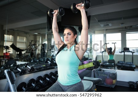 Strong, determined and beautiful woman lifting weights in gym