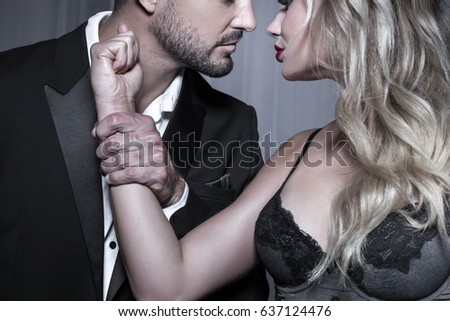 Strong dominant rich man holding blonde lovers hand, passionate couple