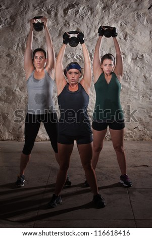 Strong females pushing kettle bell weights over their heads - stock photo