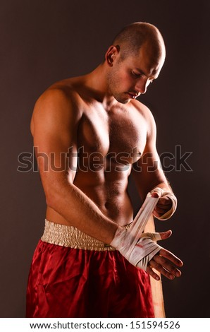 strong fighter is getting ready on gray background - stock photo