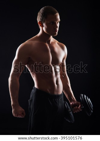 Strong, fit and sporty bodybuilder man with a dumbbell over black background - stock photo