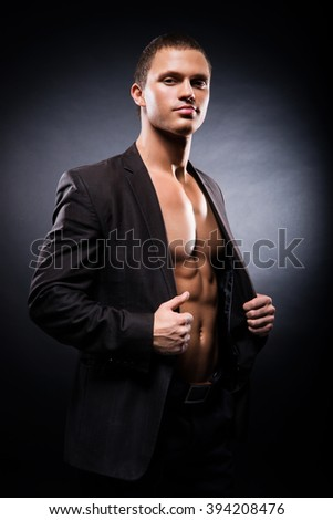 Strong, fit and sporty stripper man over black background - stock photo