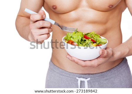 Strong fitness man holding a bowl of salad, isolated on white background - stock photo