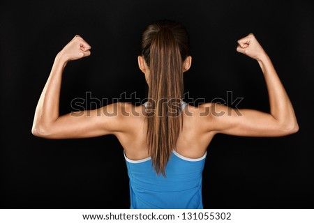 Strong fitness woman showing back and biceps muscles strength. Fit girl fitness model isolated on black background. - stock photo