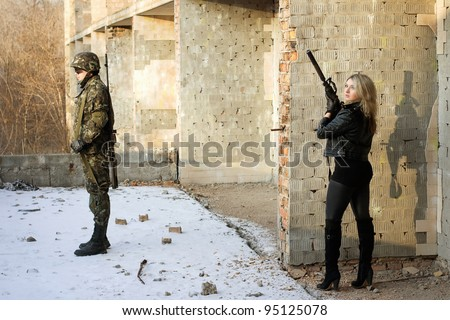 Strong girl aim at a back of soldier - stock photo