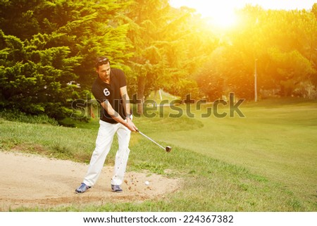 Strong golf shot of handsome player standing on golf course, golfer on sand trap hitting golf ball to the hole, golfer man hitting golf ball standing on beautiful green course at sunny evening - stock photo