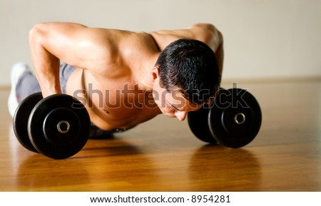 Strong, handsome man doing push-ups on dumbbells