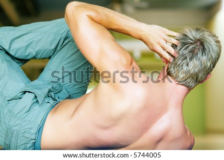 Strong, handsome man doing sit-ups - stock photo