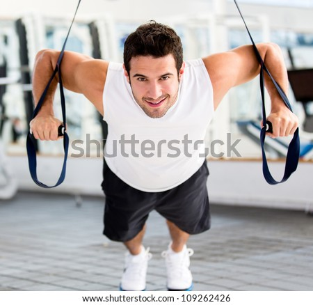 Strong handsome man exercising at the gym - stock photo