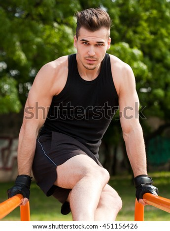 Strong handsome young guy doing bar street workout.