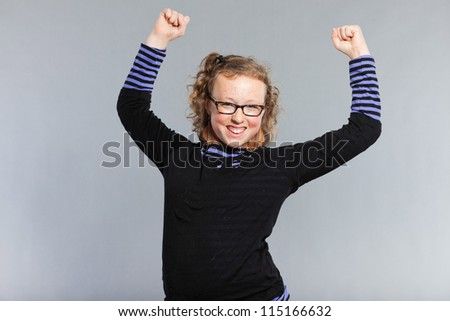 Strong happy funny teenage girl with curly blonde hair. Wearing glasses. Expressive face. Studio shot isolated on grey background. - stock photo