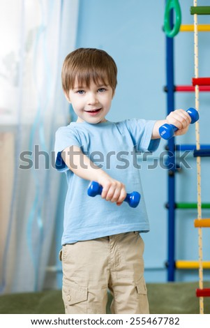 Strong kid boy exercising with dumbbells. Healthy life, sportive child. - stock photo