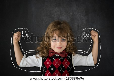 Strong kid in class. Happy child against blackboard. Education concept - stock photo